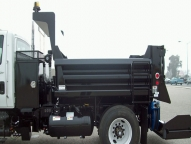 SL316 Dump Body show with 1/2 cab shield, fold-down ladder and spill apron.